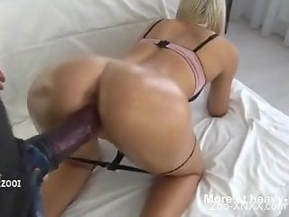 Oily booty babe getting banged by a horse cock dildo