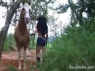Latina in a snakeskin hat blows a hung horse