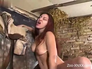 Busty redhead fingers herself in front of a horse